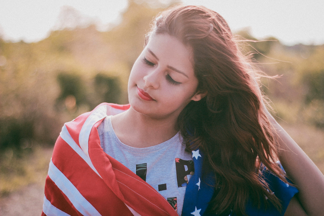 A photo of a girl with red hair wearing an American flag around her body, with green and brown plants in the background.