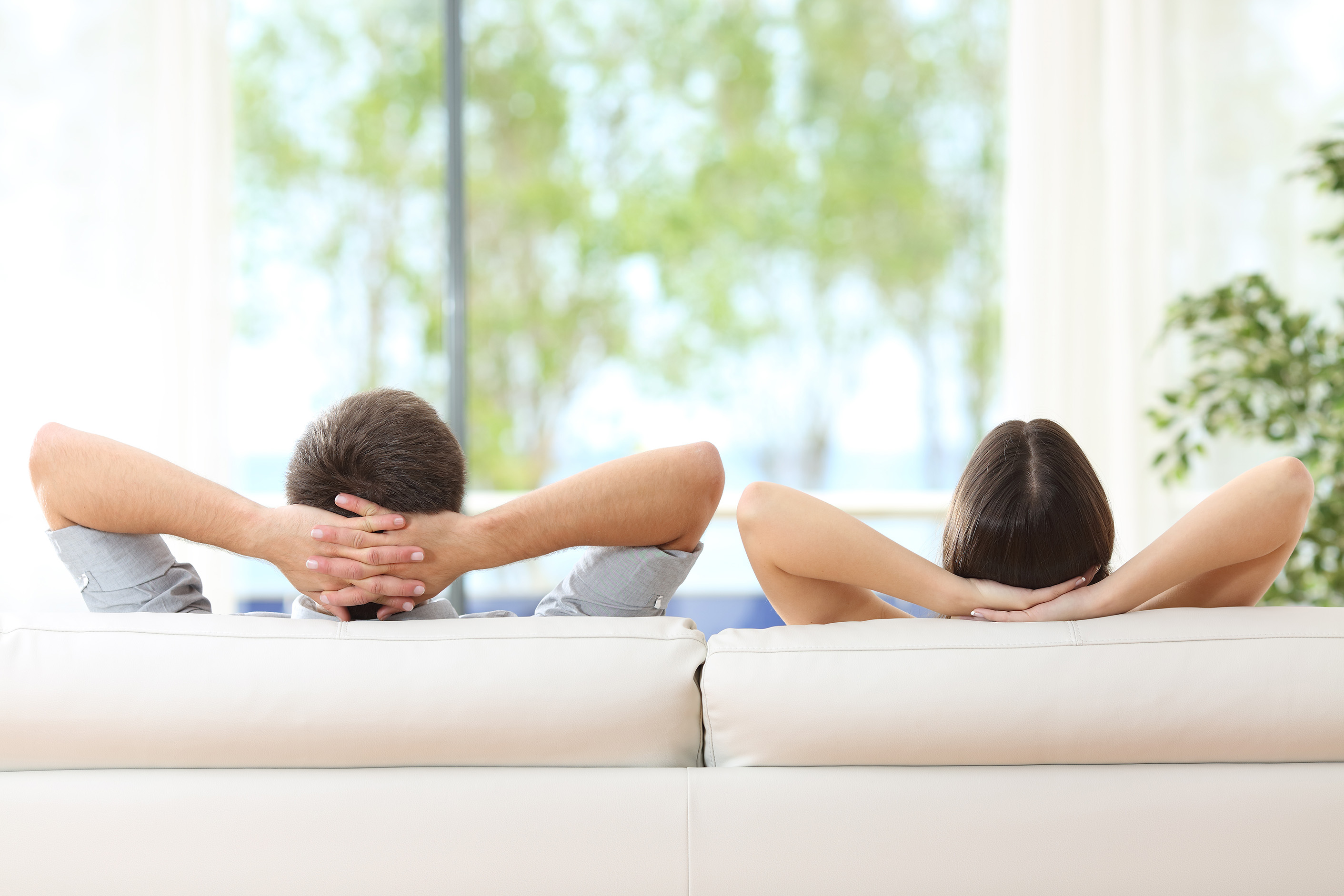 A photo of a straight couple relaxing on a beige couch in their home, looking out an overexposed green yard