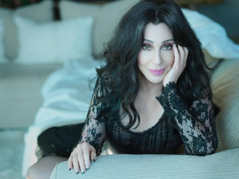 A headshot of Cher, with a lace shirt, smiling on a couch, with pink lipstick.