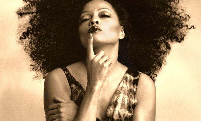 A vintage, sepia-tone photo of Diana Ross, touching her lip and smirking.