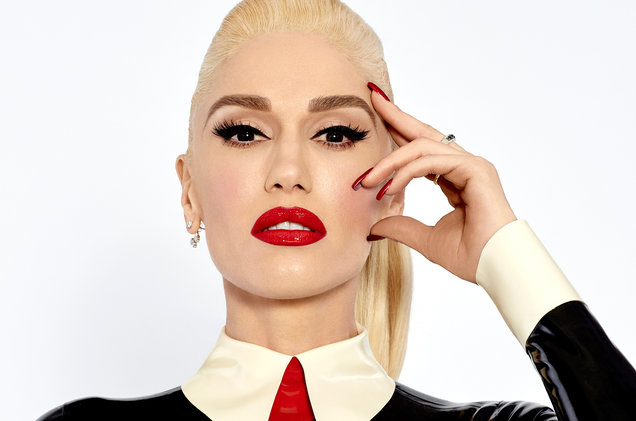 A straight headshot of Gwen Stefani, behind a white backdrop, wearing red lipstick and a black, white and red suit.
