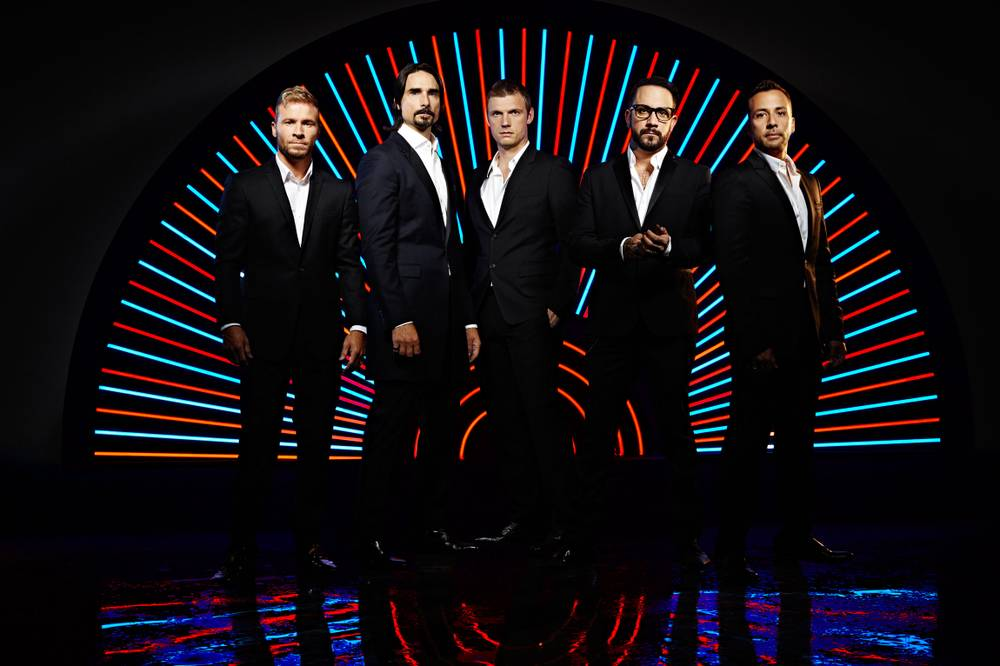 A photo of the Backstreet Boys on a black stage, with neon lights behind them. They are all in black suits.