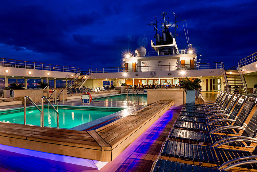 A photo of the Zenith Ship rooftop deck, where the new Open Sea Cruises party takes place. The picture is shot at night, with the deck lit up in purple, and withe a green-lit pool in the center.