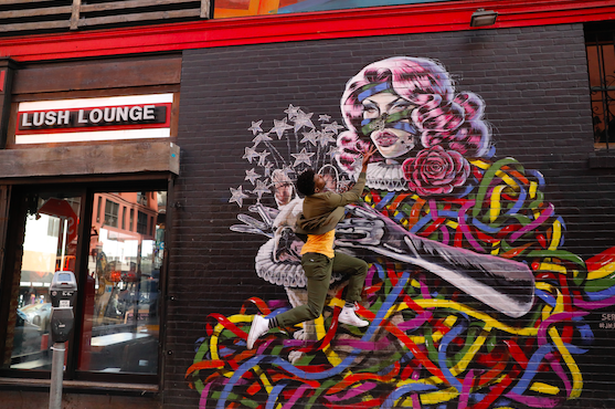 Artist Sergei Gay Jr is leaping in front of a mural he painted, next to Lush Lounge, in San Francisco.