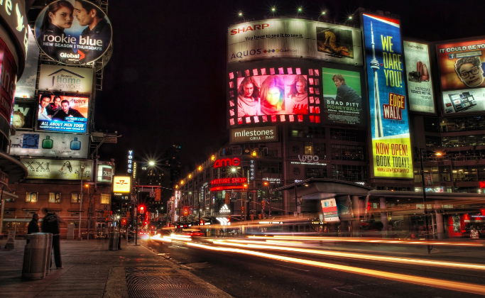 Kensington Square in Toronto lit up at night, with signs and stores that make it looks like a smaller version of Times Square in New York City
