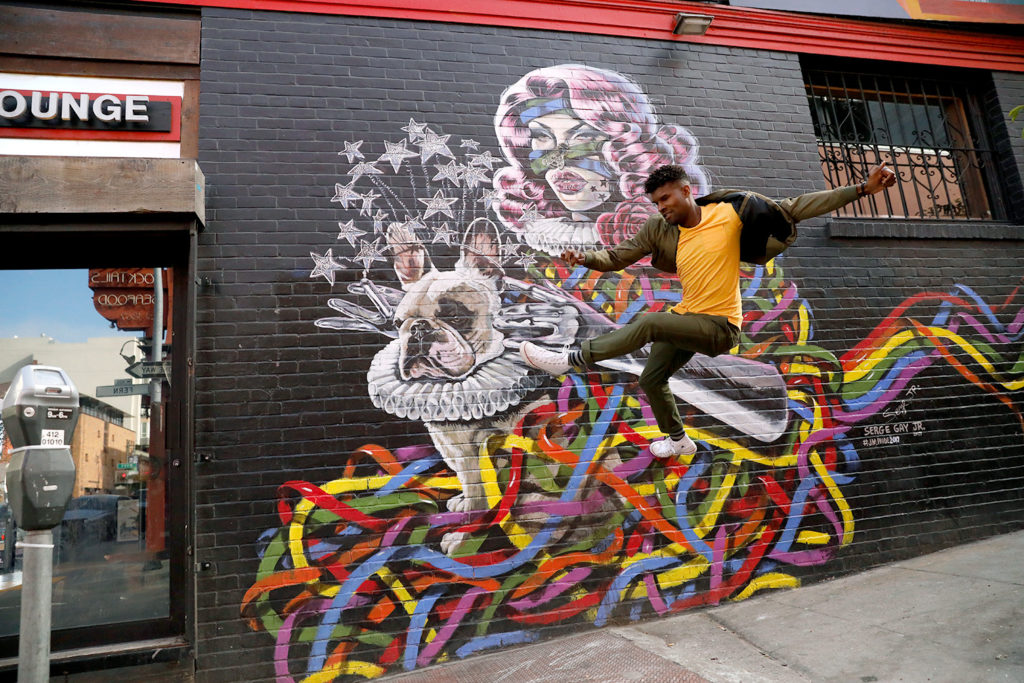 Serge Jr, a San Francisco based Artist, is jumping in the air, in a yellow, shirt, in front of one of his colorful murals of a dog in a ballerina outfit.
