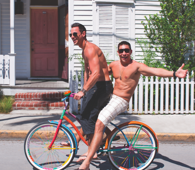 Two shirtless men smile on a bike in Key West.