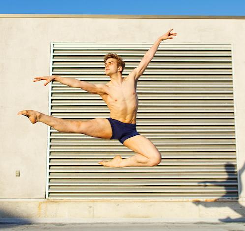 Queer ballet dancer Myles Thatcher shirtless, doing a dance jump in front of a garage.