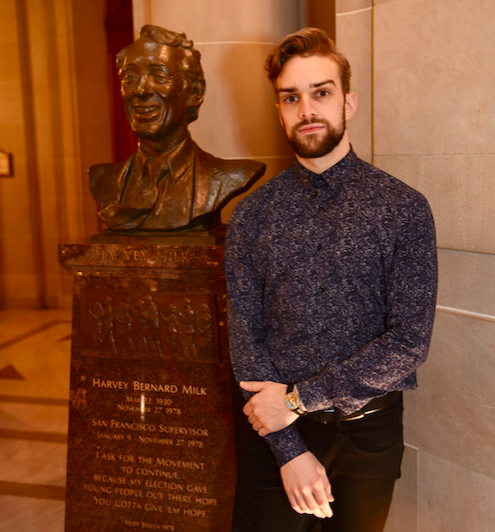 Gay dancer Myles Thatcher poses with a status of Harvey Milk in San Francisco's city hall.