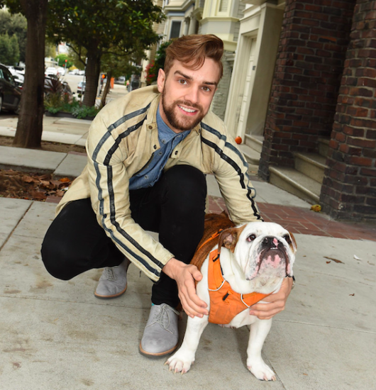 Dancer Myles Thatcher poses in a San Francisco street with a bulldog that is wearing an orange harness.