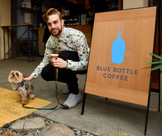 Myles Thatcher poses with a yorkie in front of a sign for Blue Bottle Coffee.