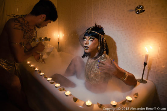 A drag queen poses in Egyptian attire, in a bathtub, with an assistant photographing her.
