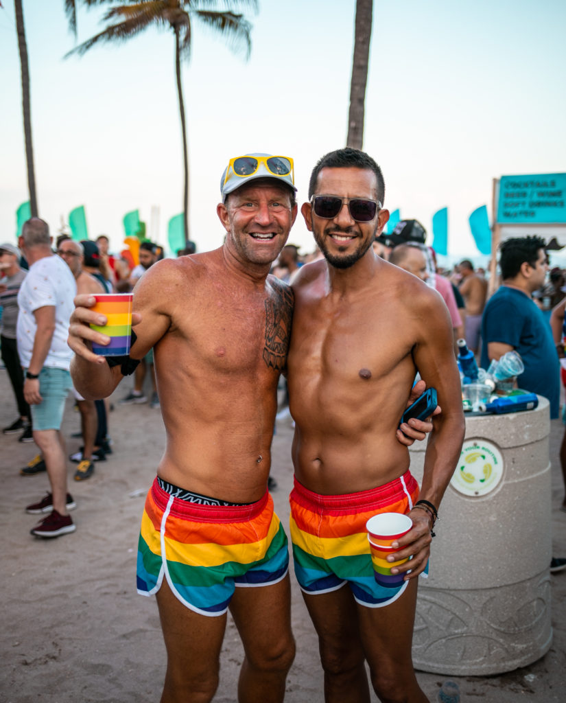 A gay shirtless couple in rainbow shorts pose for a photo on the gay beach in Fort Lauderdale