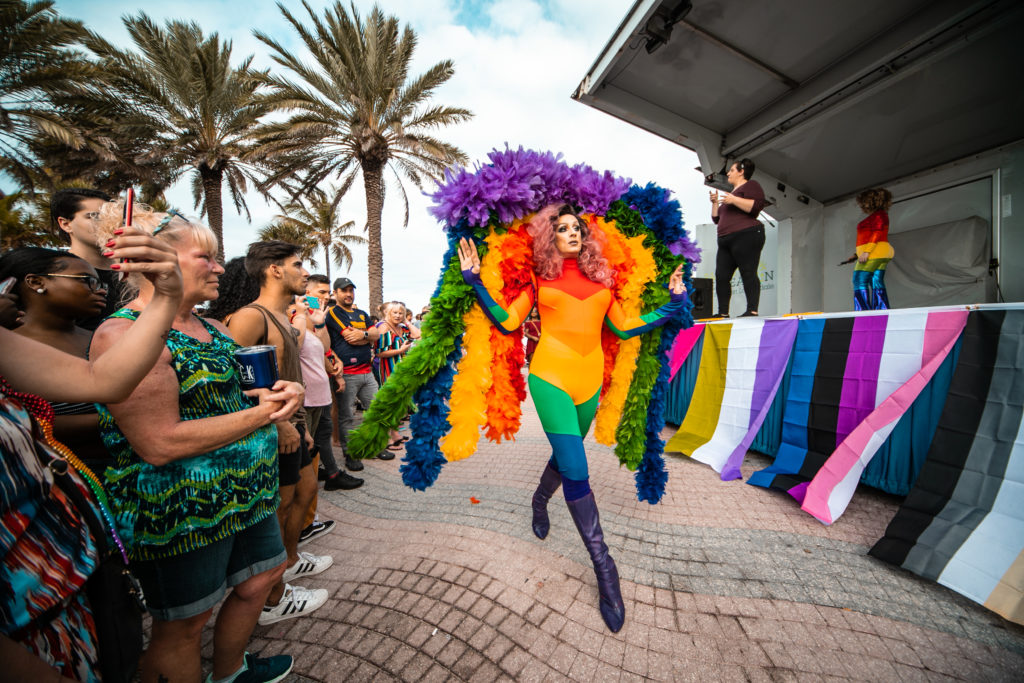 A photo of a drag queen wearing a rainbow jumpsuit strutting in front of a crowd in Fort Lauderdale, with palm trees in the background.