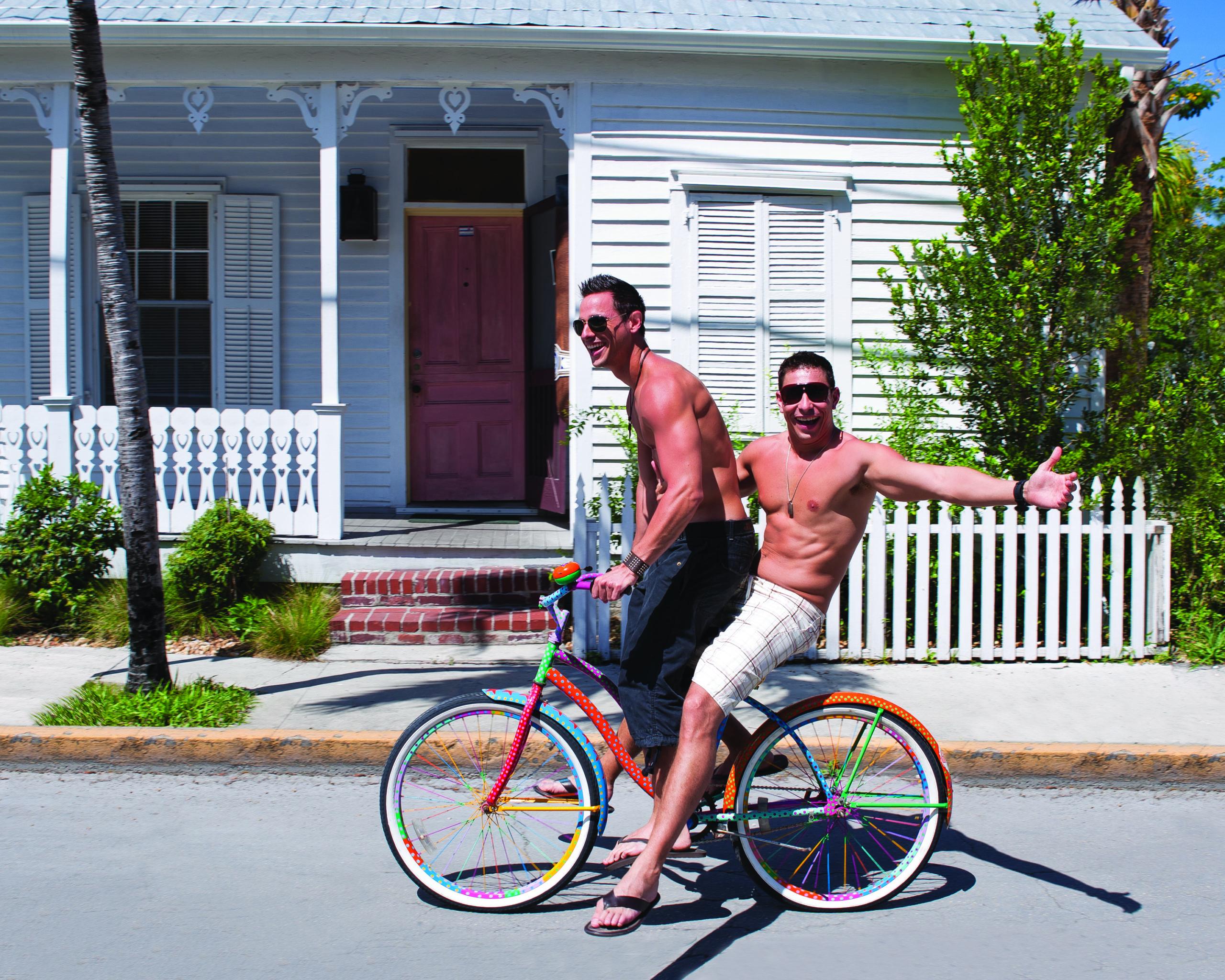 Two gay shirtless men ride a bike in Key West