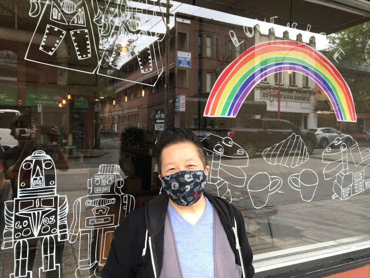 Candie Tanaka in front of his 'Love is Love' vinyl artwork on the window of Propaganda Coffee