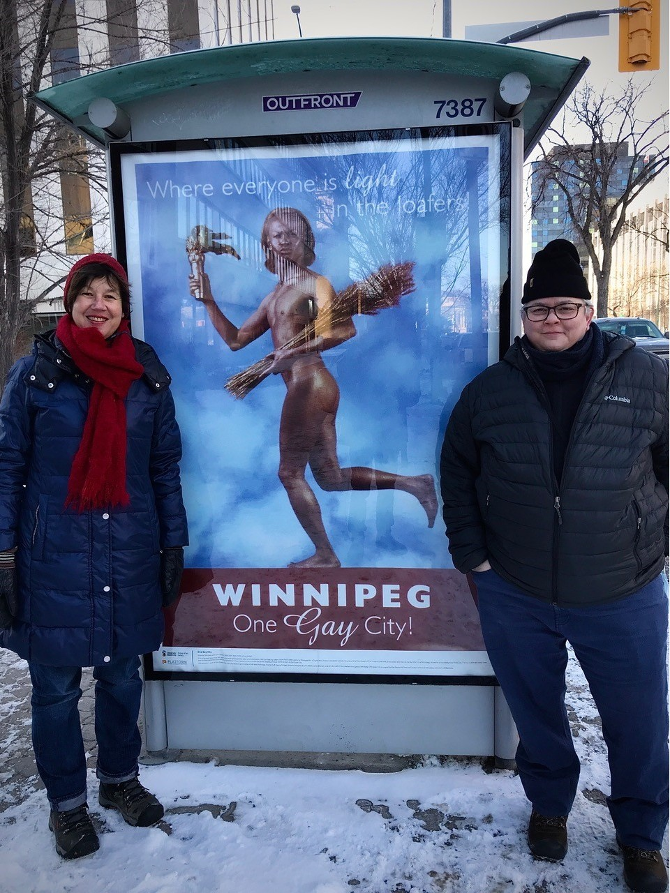 Artists Shawna Dempsey and Lorri Millan besides one of their Winnipeg posters