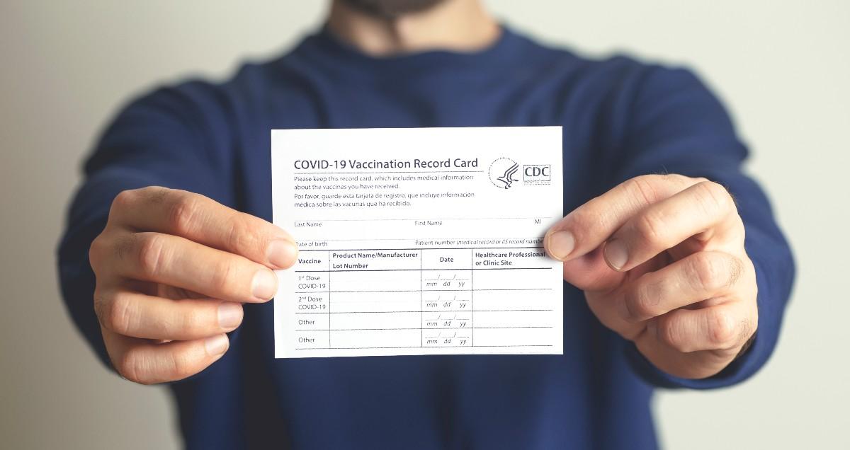 A man holds a vaccine card